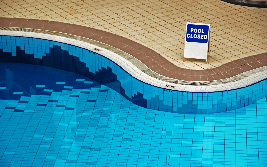"Empty swimming pool with a ""Pool closed"" sign. Opening pools can be challenging during a pandemic."