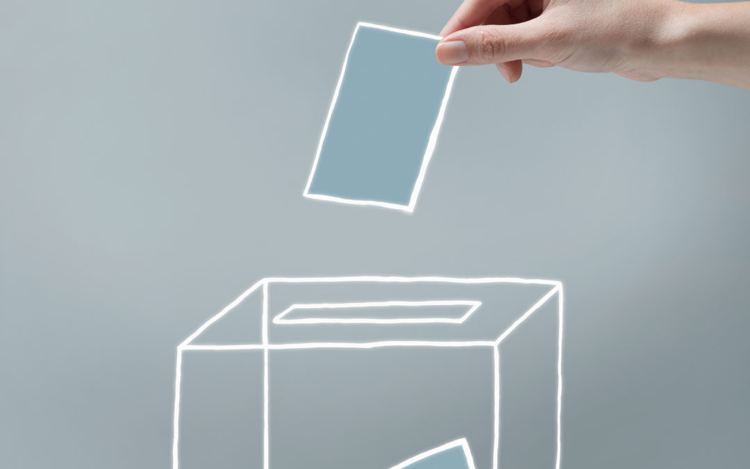 Young woman's hand casting a ballot into a voting box.