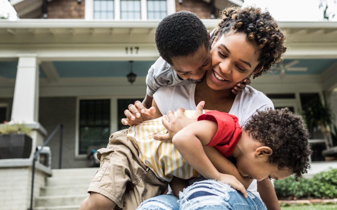 Single mother playing with young sons in front of house
