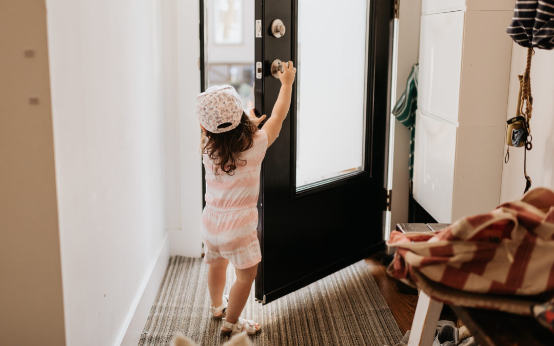 Toddler opening front door of house